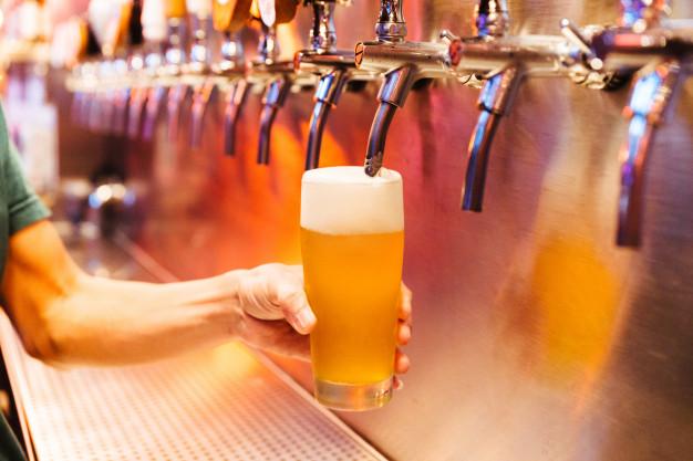 homem-derramando-cerveja-artesanal-de-torneiras-de-cerveja-em-vidro-congelado-com-espuma